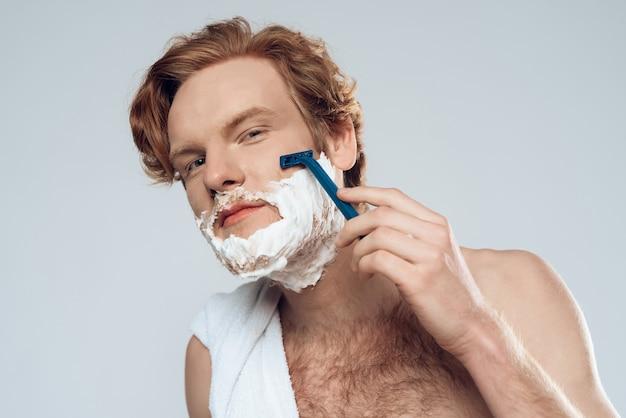 El chico pelirrojo joven afeita cuidadosamente con la maquinilla de afeitar. higiene masculina.