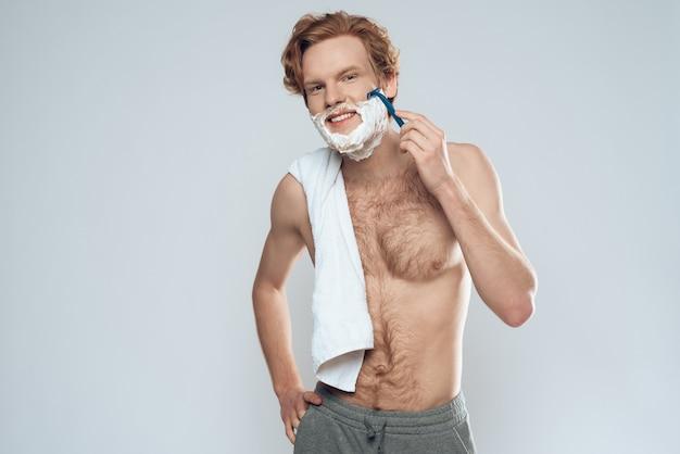 El chico pelirrojo joven afeita cuidadosamente con la maquinilla de afeitar.