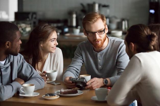 Chico pelirrojo mostrando fotos de cámara a diversos amigos en café