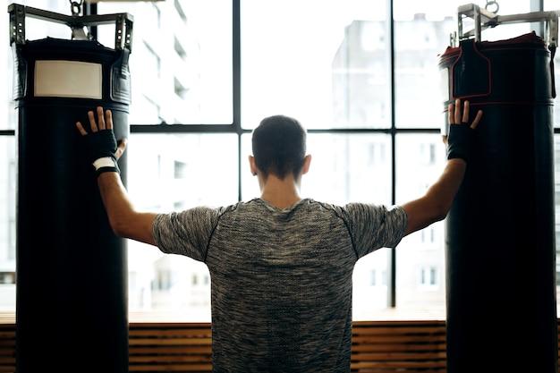 Chico de pelo oscuro se encuentra entre dos sacos de boxeo contra el fondo de ventanas panorámicas en el gimnasio de boxeo.