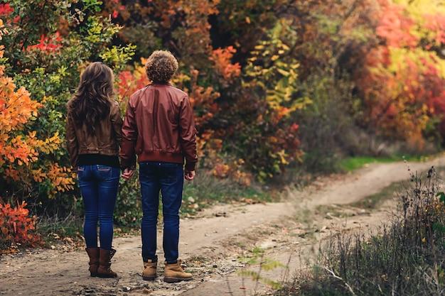Chico de pelo rizado y chica rubia en otoño de pie desplegado con la espalda en la carretera