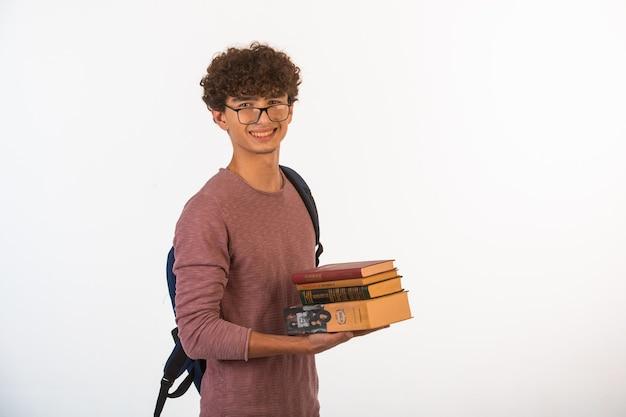 Chico de pelo rizado en gafas ópticas sosteniendo libros escolares y parece motivado