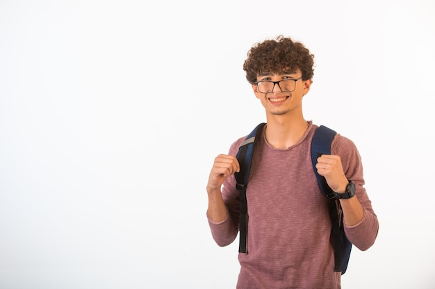 Chico de pelo rizado con gafas ópticas sosteniendo su mochila está seguro y motivado, vista frontal.