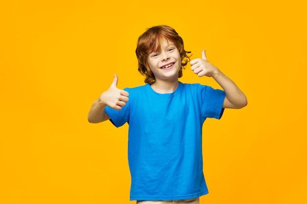 Chico de pelo rojo camiseta azul amarillo fondo aislado pecas y una mirada feliz desde el pulgar