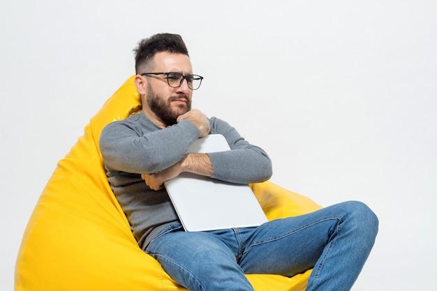 Chico en pensamientos mientras está sentado en la silla del puf amarillo