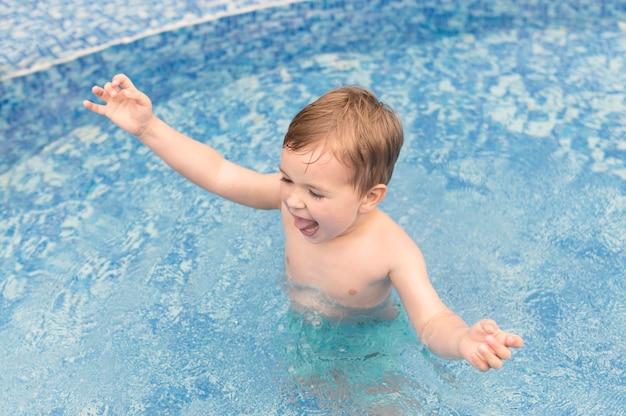 Chico en la piscina divirtiéndose