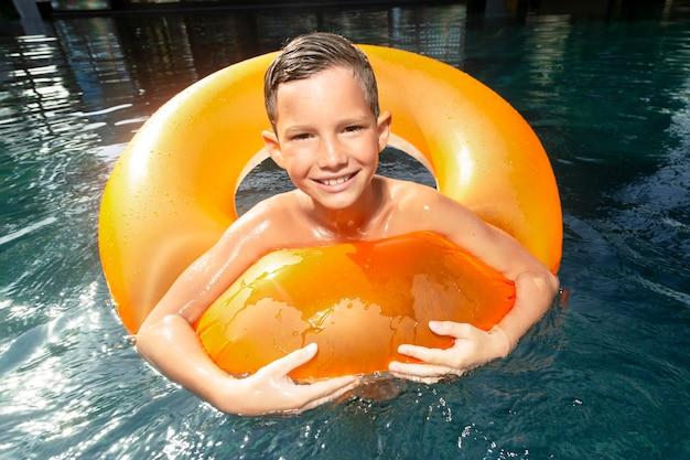 Chico en la piscina con flotador de piscina