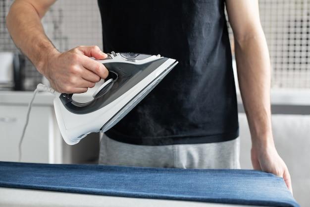 Un chico planchando ropa antes de salir