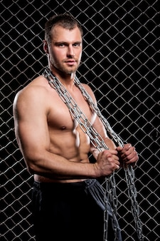Chico poderoso con una cadena mostrando sus músculos