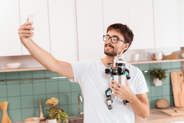 Un chico posando con un robot en una cocina moderna y ligera.