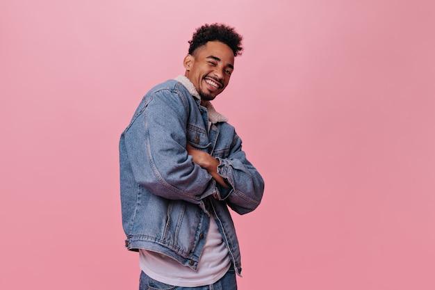 Chico positivo en chaqueta de mezclilla guiñando un ojo en la pared rosa