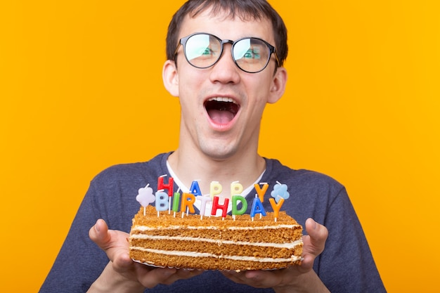 Chico positivo divertido en vasos tiene en sus manos un pastel casero con la inscripción feliz cumpleaños