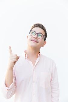 Chico positivo en gafas apuntando el dedo hacia arriba