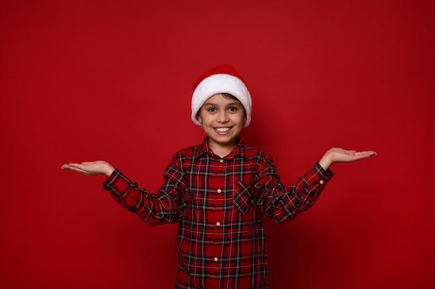 Chico preadolescente alegre guapo, niño divertido con sombrero de santa y camisa a cuadros roja tiene un espacio de copia imaginaria en sus manos con las palmas hacia arriba, aislado sobre fondo rojo. concepto de navidad y año nuevo para anuncios.