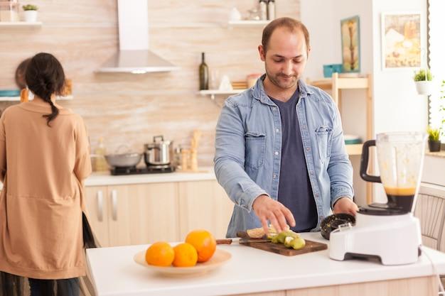 Chico preparando sabroso batido en cocina con licuadora. estilo de vida saludable, despreocupado y alegre, comiendo dieta y preparando el desayuno en una acogedora mañana soleada