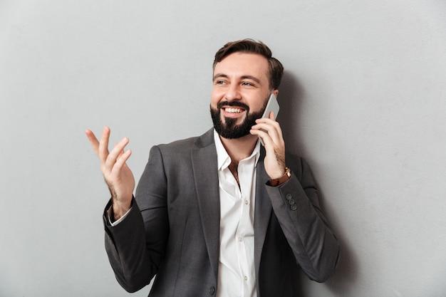 Chico profesional positivo en ropa formal chateando móvil gesticulando mientras usa el teléfono celular, aislado en gris