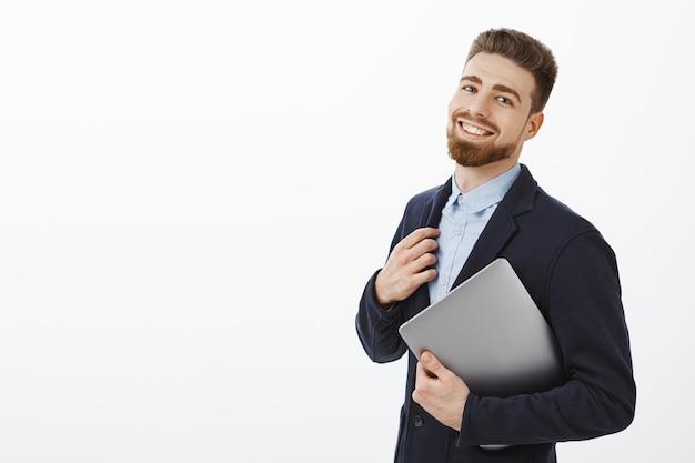 El chico puede hacer frente a cualquier tarea sintiéndose seguro de sí mismo y complacido tocando el traje sosteniendo la computadora portátil en el brazo de pie medio volteado sobre la pared gris mirando encantado y satisfecho con su propio plan exitoso