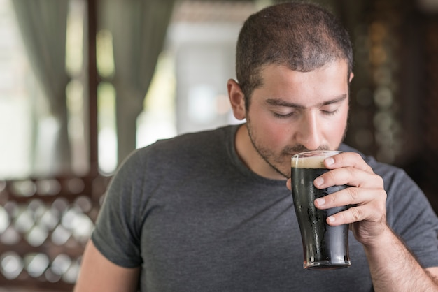 Chico que huele cerveza en pub