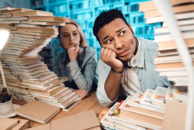 Chico de raza mixta india y chica blanca están mirando libros.