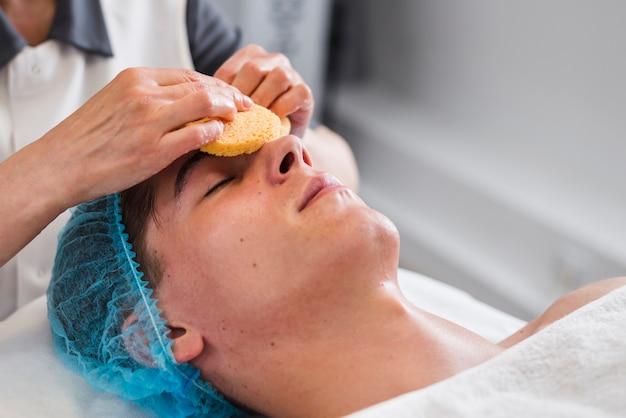 Chico recibiendo tratamiento facial en salón de belleza