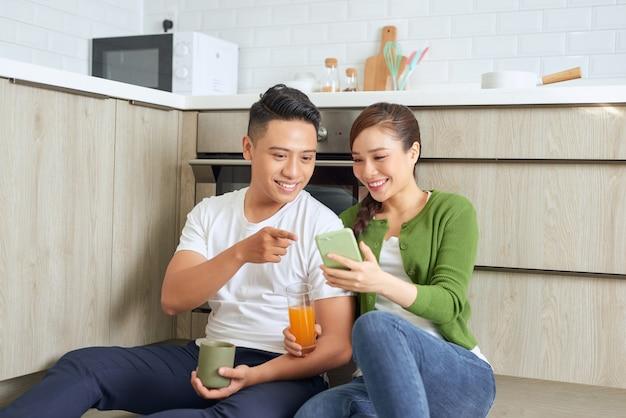 Chico riendo con una chica sentada en el suelo de la cocina con tazas de café y zumo de naranja