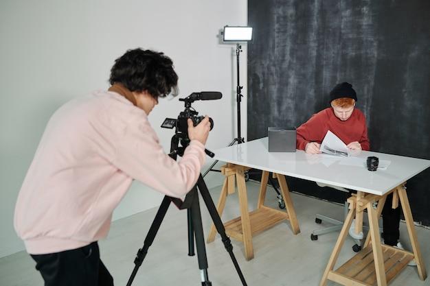 Chico en ropa casual agachándose frente a la cámara de video mientras dispara un vlogger masculino sentado junto al escritorio en el estudio