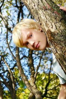 Chico rubio atractivo detrás de un árbol