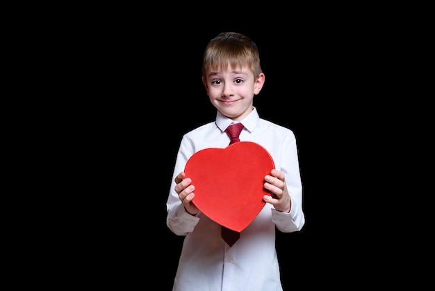 Chico rubio con camisa y corbata sosteniendo una caja roja en forma de corazón. amor y concepto de familia.