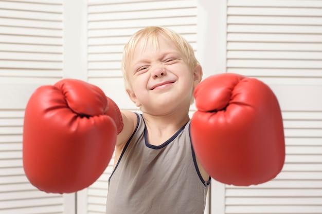 Chico rubio encantador en guantes de boxeo rojos. deportes