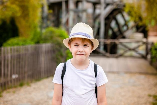 Chico rubio con estrabismo en el sombrero de paja en el parque de atracciones