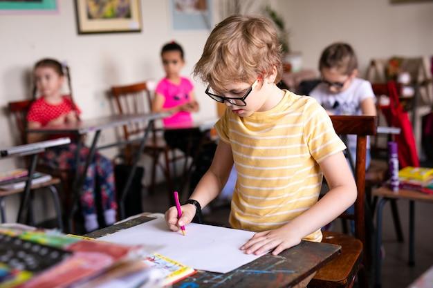 Chico rubio con gafas de dibujo. grupo de alumnos de primaria en el aula en clase de arte.