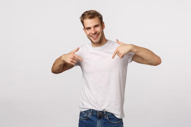 Chico rubio guapo con ojos azules y camiseta blanca apuntando a sí mismo