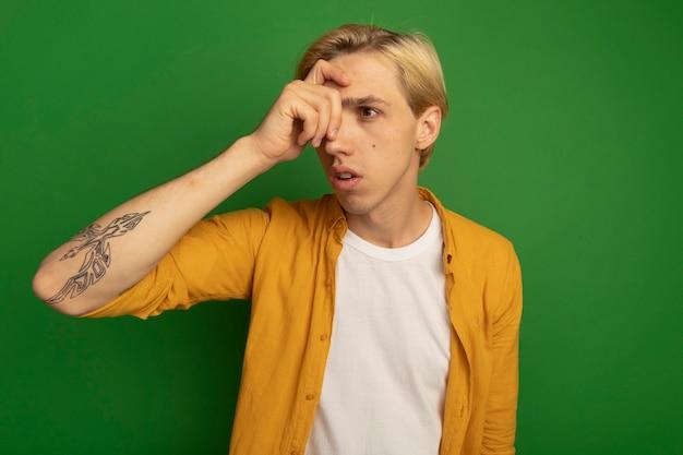 Chico rubio joven mirando al lado con camiseta amarilla poniendo la mano en la frente aislada en verde
