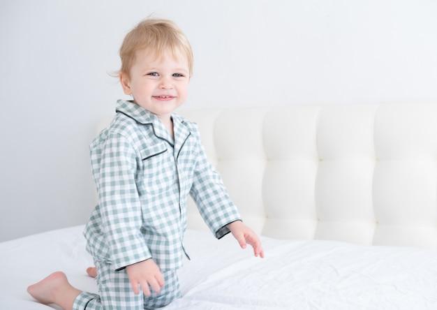Chico rubio lindo niño sano en pijama a cuadros divirtiéndose acostado en la cama blanca en casa.