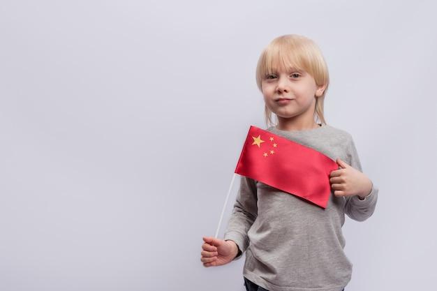 Chico rubio lindo tiene una bandera de china. educación en china. aprendiendo chino