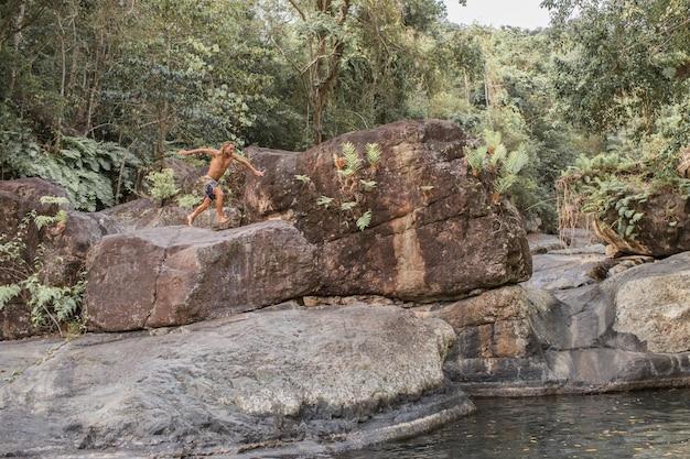 El chico salta de una piedra al agua.