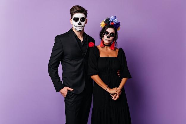 Chico serio con la cara pintada y chica con flores en el pelo posando para retrato para halloween.