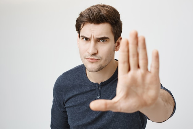 Chico serio disgustado extiende la mano para mostrar parada o advertencia, desaprueba la acción