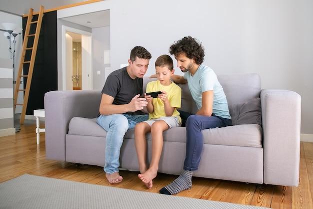 Chico serio jugando juegos en línea en el teléfono celular, sus dos papás sentados cerca de él y mirando la pantalla. familia en casa y concepto de comunicación.