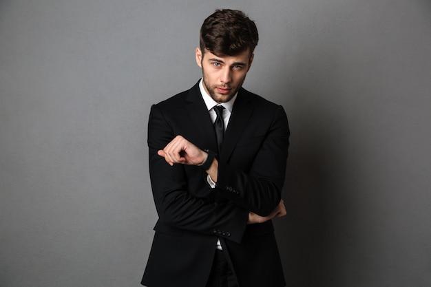 Chico serio serio con traje negro que controla la hora en su reloj de pulsera,