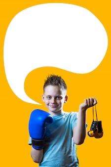 Chico severo en guantes de boxeo azules sobre fondo amarillo brillante