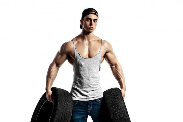 El chico sexy guapo muy musculoso mantenga neumático de goma y blanco, sobre fondo blanco, aislado