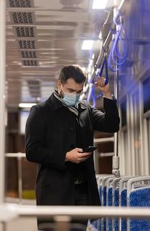 Chico solitario con una mascarilla monta un tranvía por la noche en tiempo de pandemia
