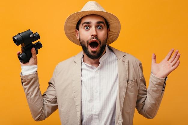 Chico con sombrero mira conmocionado a la cámara y sosteniendo binoculares