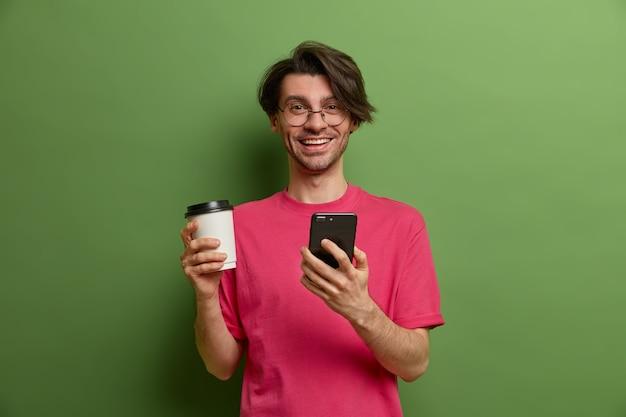 Chico sonriente alegre busca cosas necesarias en la tienda en línea, usa la aplicación de teléfono inteligente, navega por las redes sociales, bebe café aromático de una taza de papel, tiene un peinado moderno, posa en interiores