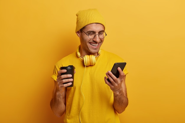 Chico sonriente alegre se ve gracioso video a través de teléfono inteligente, bebe sabrosa bebida caliente de taza de papel, usa sombrero amarillo y camiseta