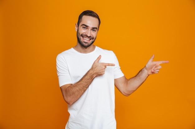 Chico sonriente en camiseta apuntando con el dedo a un lado mientras está de pie, aislado en amarillo
