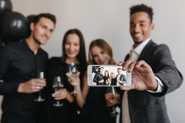 Chico sonriente con corte de pelo de moda haciendo selfie con amigos durante fest