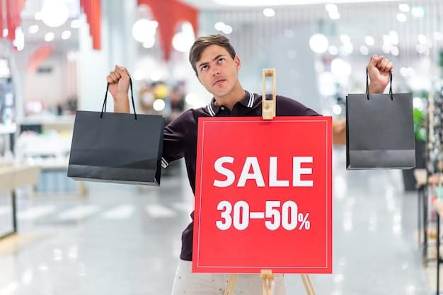 Chico sonriente joven posando con una camiseta burdeos y pantalones cortos beige con bolsas de colores. posando en el fondo de la pancarta con la inscripción venta y descuentos de hasta 30-50 por ciento