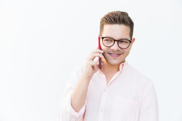Chico sonriente pensativo en anteojos llamando al celular